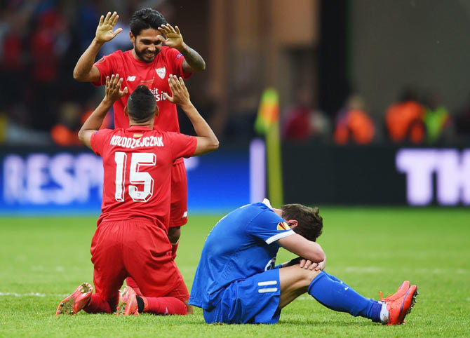Sevilla's Benoit Tremoulinas celebrates with teammate Timothee Kolodziejczak as Dnipro's Yevhen Seleznyov sits dejected after their UEFA Europa League final