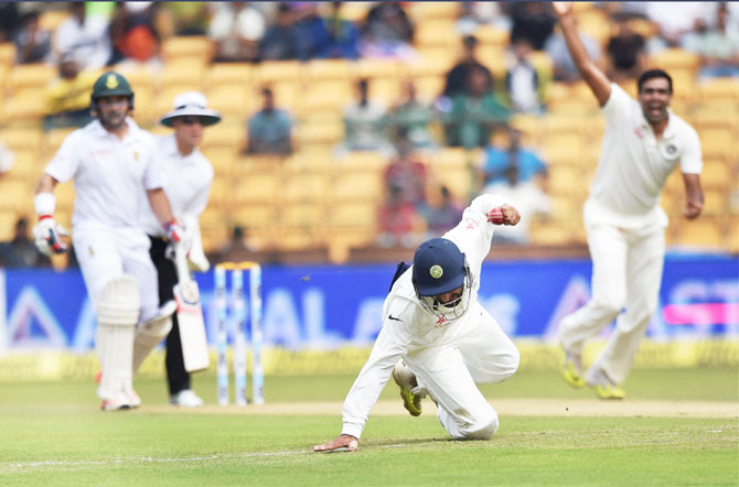 India's Cheteshwar Pujara completes a catch to dismiss South Africa's Faf Du Plesis