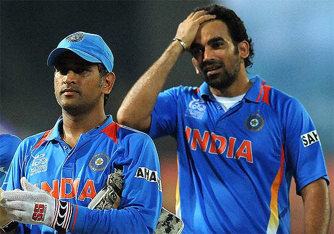India's MS Dhoni along with teammate Zaheer Khan walk back to the pavilion after a game