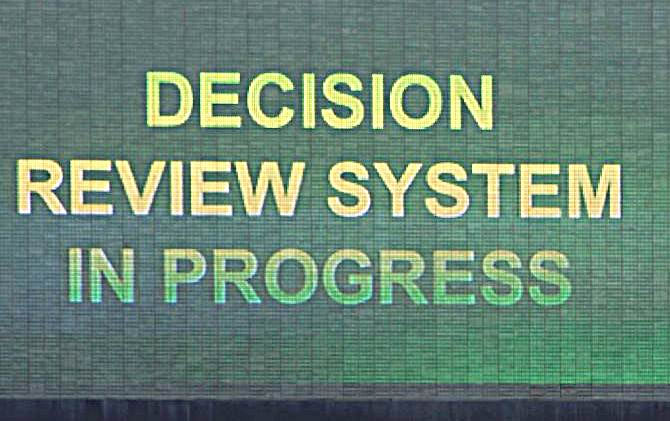 A giant screen at a cricket venue flashes the request for review during a match