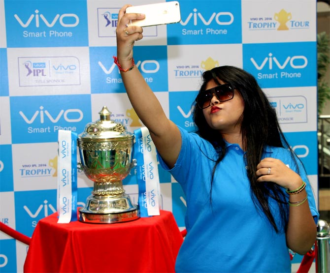 A fan poses with the IPL trophy