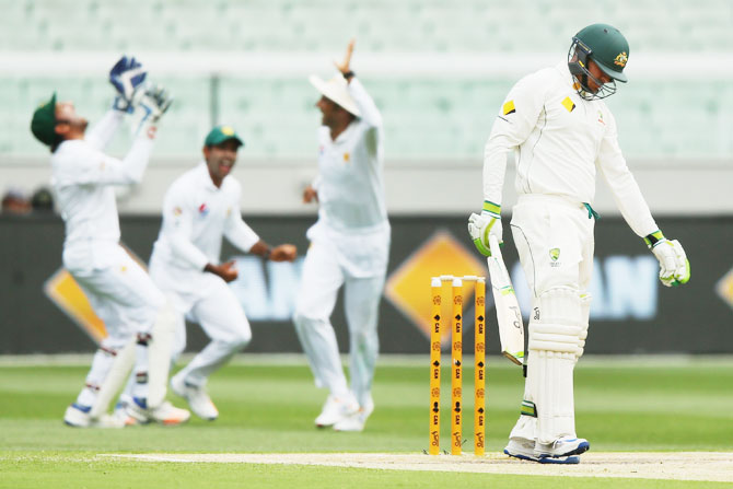 Australia's Usman Khawaja reacts after being caught out for 98
