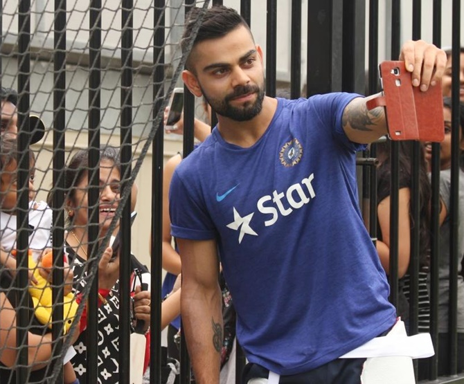 India's Virat Kohli poses for a selfie with fans