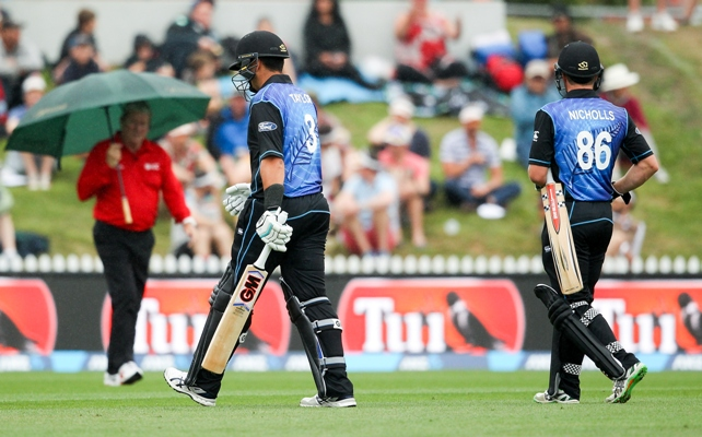 Ross Taylor (center) and Henry Nicholls (right) of New Zealand leave the field
