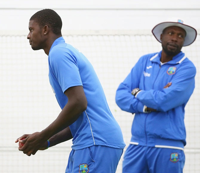 West Indies bowling consultant Curtly Ambrose (right) looks on as captain Jason Holder bowls in the nets