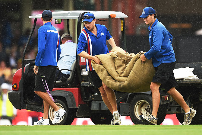 Groundsmen bring the covers on as rain delays play on Day 2 of the third Test match between Australia and the West Indies at Sydney Cricket Ground in Sydney on Monday