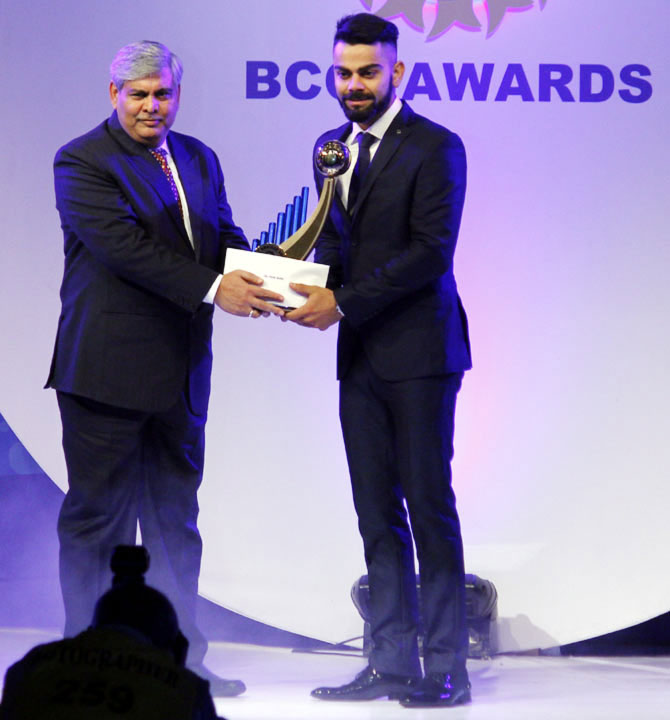India's Test captain Virat Kohli accepts the Polly Umrigar Trophy for Cricketer of the Year from BCCI president Shashank Manohar