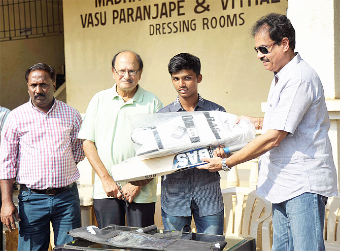 Pranav Dhanawade (centre) is presented with a batting kit by former India captains Dilip Vengsarkar (right) and Ajit Wadekar (2nd from right) during a felicitation ceremony on Wednesday