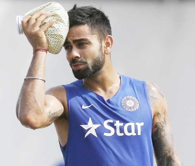 India's captain Virat Kohli uses an ice pack on his head during a practice session