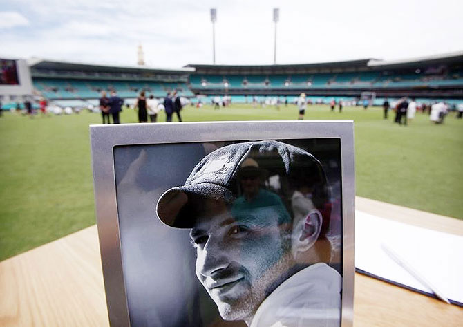 A photograph of Australian cricketer Phillip Hughes is displayed next to a condolences book at the Sydney Cricket Ground (SCG) December 3, 2014