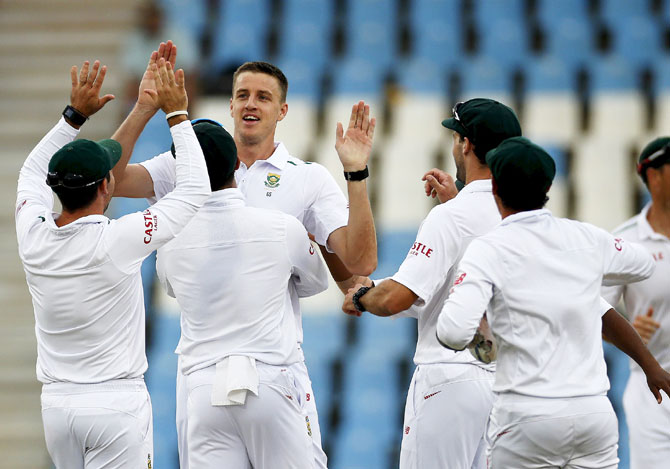 South Africa's Morne Morkel (3rd from left) is congratulated by teammates after he bowled out England's captain Alastair Cook during the fourth Test match at Centurion, in Pretoria on Monday