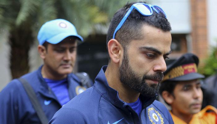 India's captain Virat Kohli and then head coach Anil Kumble in the background