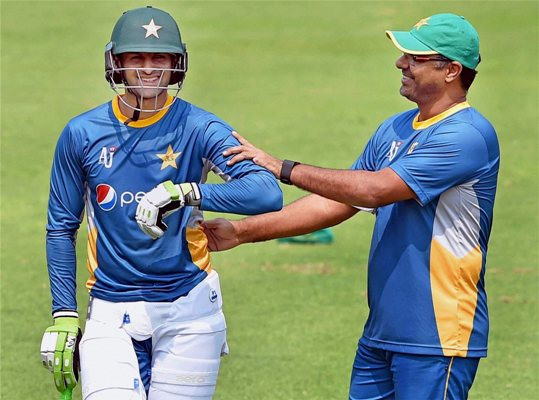 Pakistan coach Waqar Younis shares a light moment with Shoaib Malik during their training session