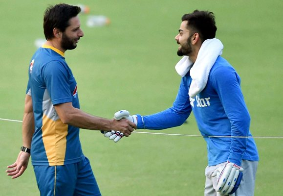 Virat Kohli greets Pakistan's Shahid Afridi at a training session. Photograph: PTI