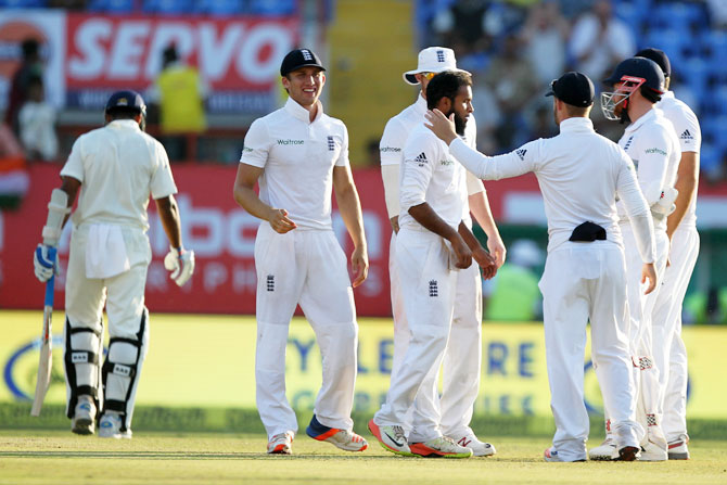 England's Adil RAshid (centre) celebrates with teammates after scalping the wicket of India's Murali Vijay on Day 3 of the first Test match in Rajkot on Friday