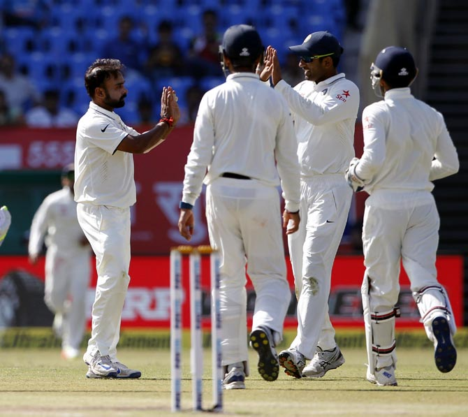 Amit Mishra, left, celebrates with team mates after taking the wicket of Haseeb Hameed