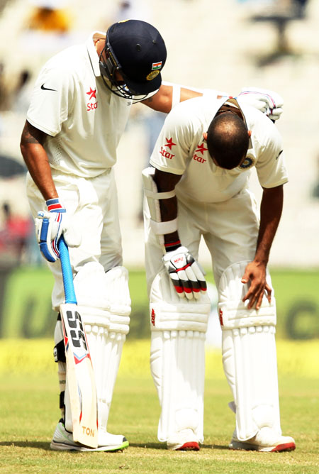 Shikhar Dhawan (right) is comforted by teammate Rohit Sharma after getting hit on the thumb, on Day 3 of the 2nd Test in Kolkata on Sunday