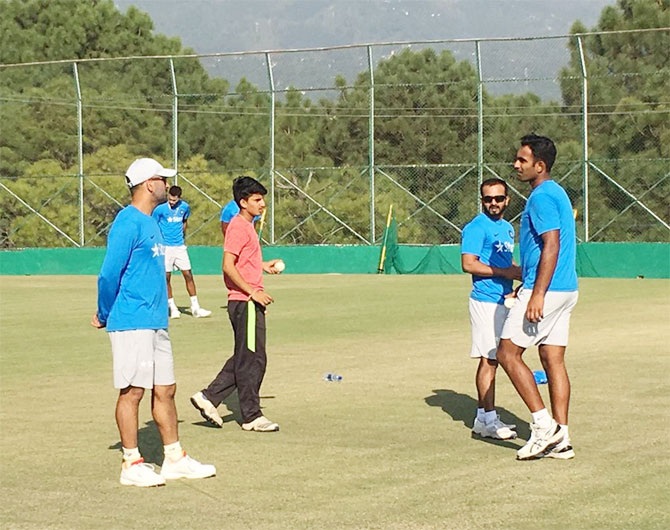 India's One-day skipper Mahendra Singh Dhoni speaks to teammates at a practice session in Dharamsala on Saturday