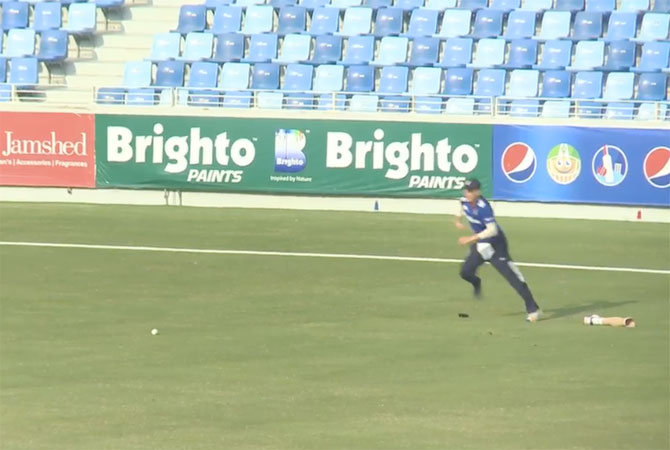 A video grab of Liam Thomas hopping to field the ball even as he loses his prosthetic limb