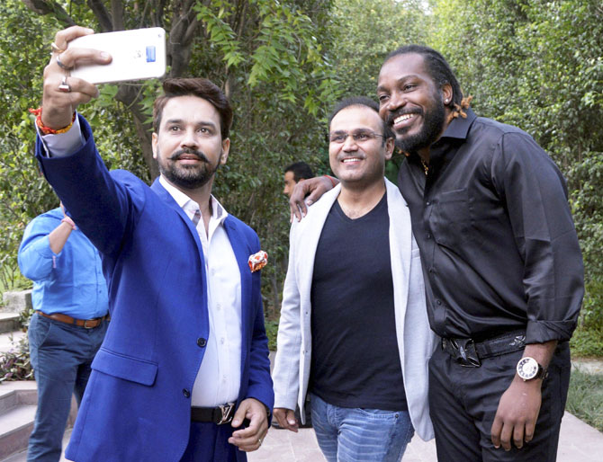 BCCI President Anurag Thakur takes a selfie with former India cricketer Virender Sehwag and West Indies cricketer Chris Gayle at the launch of Gayle's autobiography 'Six Machine' in Gurgaon on Friday