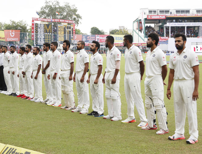 Indian players stand for the national anthem before the opening day's play of the first Test match against New Zealand at the Green Park stadium in Kanpur on Thursday