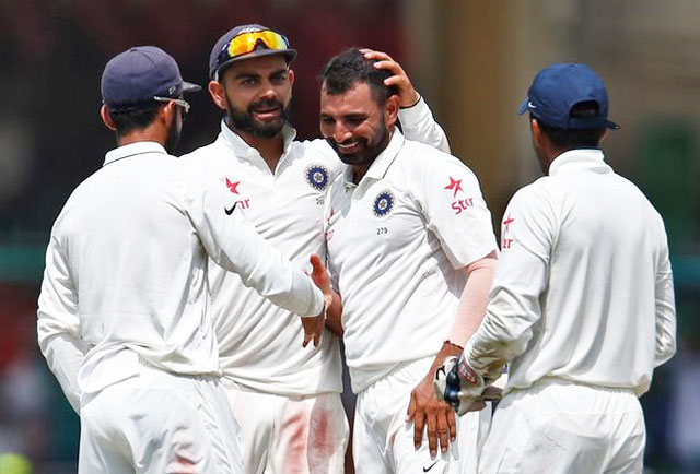 India's Mohammed Shami celebrates with teammates after taking the wicket of New Zealands's Mark Craig on Monday