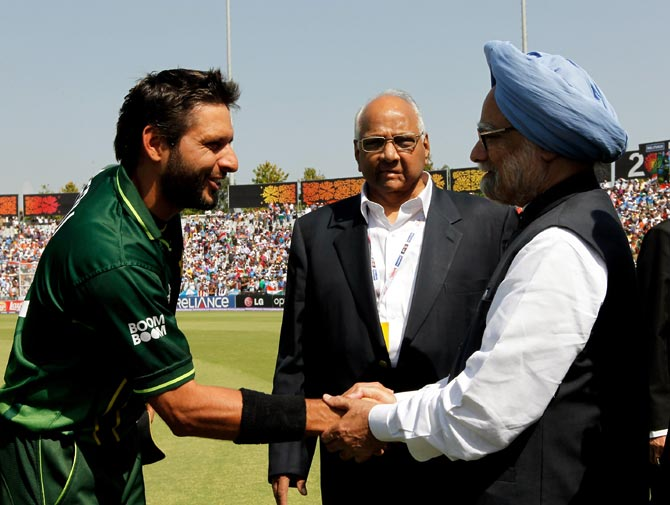A file photograph of Pakistani cricketer Shahid Afridi, left, shaking hands with India's then prime minister Manmohan Singh, as then ICC president Sharad Pawar looks, during the 2011 World Cup semi-final between India and Pakistan in Mohali, on March 30, 2011
