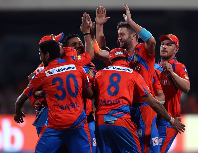 Andrew Tye celebrates with teammates after claiming the wicket of RCB's Travid Head