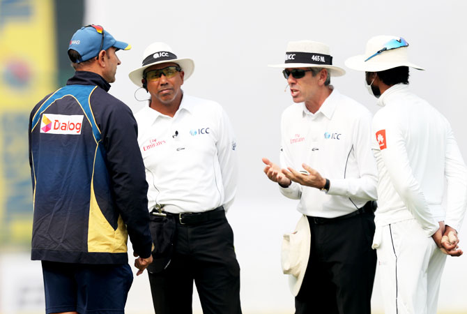 Umpire Nigel Llong speaks animatedly to Sri Lanka coach Nick Pothas as captain Dinesh Chandimal listens in