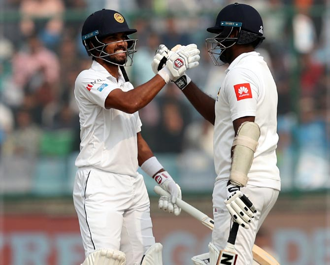 Dinesh Chandimal congratulates Angelo Mathews on completing his century on Day 3 of the 3rd Test at the Feroz Shah Kotla in New Delhi on Monday