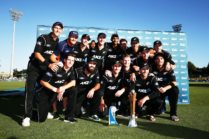 New Zealand players pose for cameras as they celebrate with the Chappell-Hadlee Trophy and the ANZ Series Trophy after winning game three of the One-Day International series against Australia at Seddon Park in Hamilton on Sunday