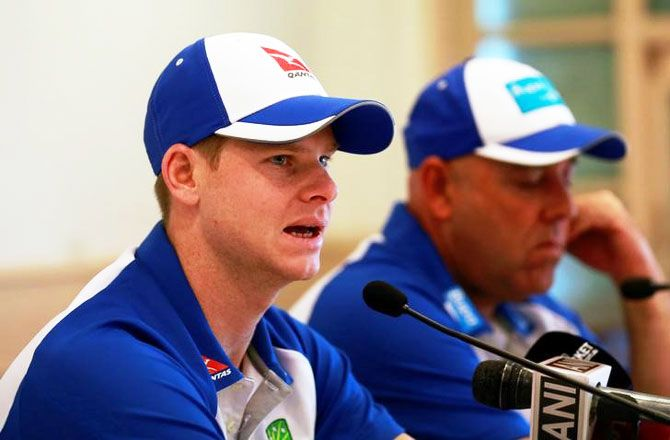 Australian cricket captain Steve Smith speaks as coach Darren Lehmann listens in at a news conference in Mumbai on Tuesday