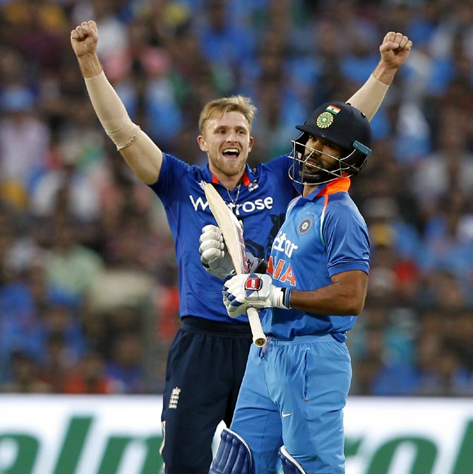 David Willey celebrates the wicket of Shikhar Dhawan during the first ODI in Pune