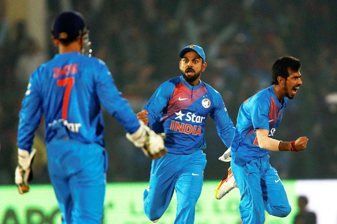India's captain Virat Kohli and Yuzvendra Chahal celebrate the wicket of England's Sam Billings