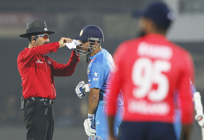 Umpire Anil Chaudhary helps Mahendra Singh Dhoni who was struggling with some dust in his eye