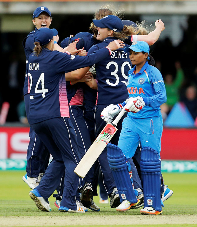 England players celebrate winning their ICC Women's World Cup match against India at Lord's on Sunday