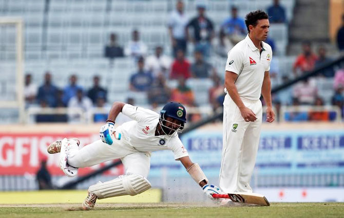 India's Cheteshwar Pujara dives to avoid being run out as Australia's Steve O'Keefe (R) looks on in despair