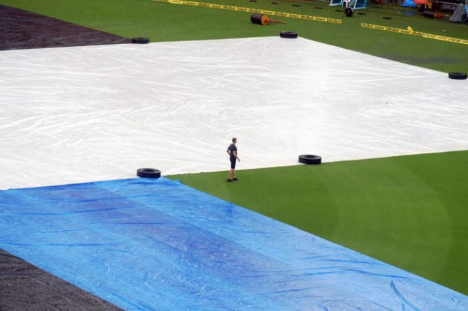 A New Zealand Cricket supporting staff takes a look at the ground which was covered owing to rain on Monday, ahead of their third and final T20 match against India at Thiruvananthapuram