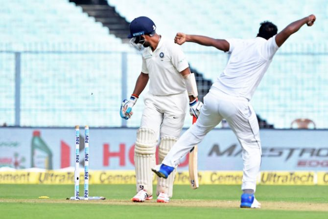 India's batsman Cheteshwar Pujara is bowled out by Sri Lankan bowler Lahiru Gamage on Day 3 of the first Test at Eden Gardens, in Kolkata on Saturday