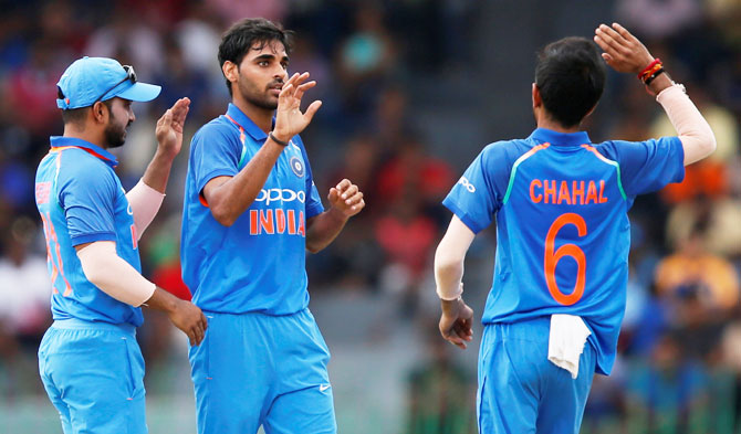 India's Bhuvneshwar Kumar celebrates with his teammates Kedar Jadhav and Yuzvendra Chahal after dismissing Sri Lanka's Niroshan Dickwella