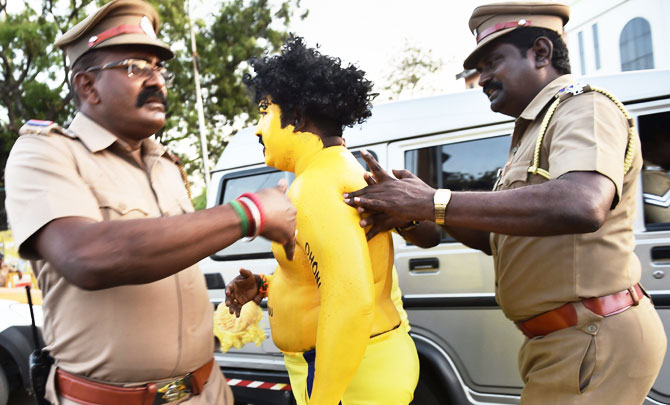 Policemen take away a fan of CSK Skipper MS Dhoni before the IPL match between Chennai Super Kings and Kolkata Knight Riders at MAC Stadium in Chennai on Tuesday
