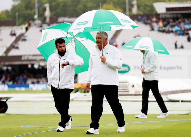 Umpires on their way to inspect the pitch at Lord's during a rain delay on Thursday