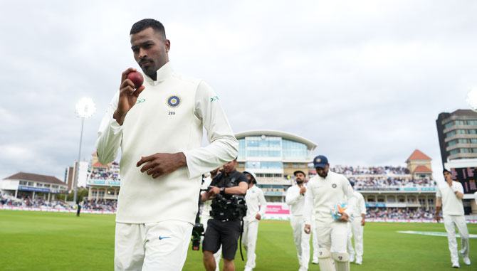 India's Hardik Pandya holds up the ball as his leads his team out after taking a five-wicket haul