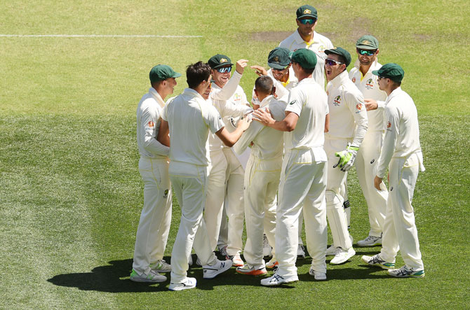 Australia's Usman Khawaja is congratulated by teammates after taking a blinder of a catch to dismiss India's Virat Kohli on Thursday