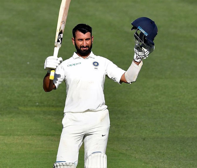 Cheteshwar Pujara celebrates after completing his century on Thursday