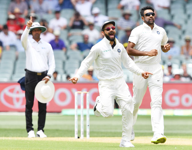 India's captain Virat Kohli and his teammate Ravichandran Ashwin celebrate the dismissal of Australia's Marcus Harris on Day 2 of the first Test at the Adelaide Oval on Friday. Ashwin ended the day with figures of 3 for 50