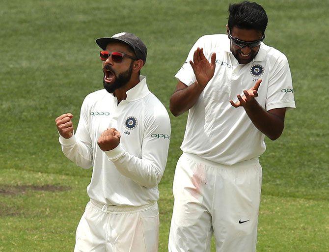 Ravichandran Ashwin, right, celebrates with captain Virat Kohli after taking the wicket of Usman Khawaja