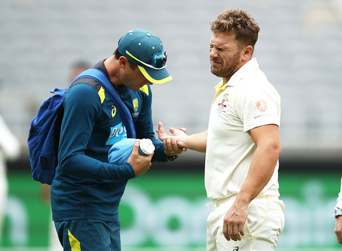 Aaron Finch reacts as he gets treatment from Australian Team Physiotherapist David Beakley after being struck on the hand by a delivery from Ishant Sharma