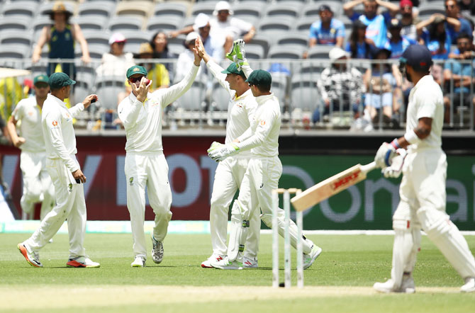 Australia's Peter Handscomb celebrates after taking a catch to dismiss India skipper Virat Kohli off the bowling of Pat Cummins