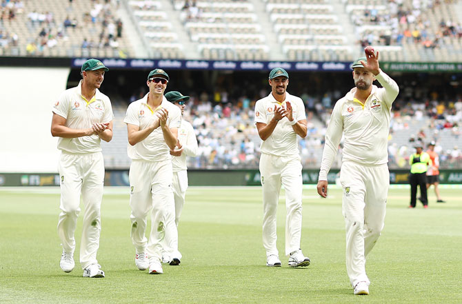 Australia's Nathan Lyon raises the ball aloft after claiming his fifth wicket at the end of India's first innings
